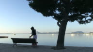 WS Shot of woman at seaside promenade / Puerto Pollenca, Mallorca, Spain