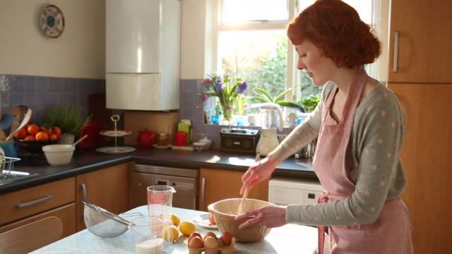 WS Shot of woman breaking eggs, sieving flour in bowl and mixing ingredients / London, Greater London, United Kingdom