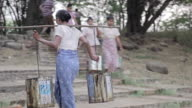 MS TS Shot of woman carrying two buckets of water from the river / Bagan, Mandalay Division, Myanmar