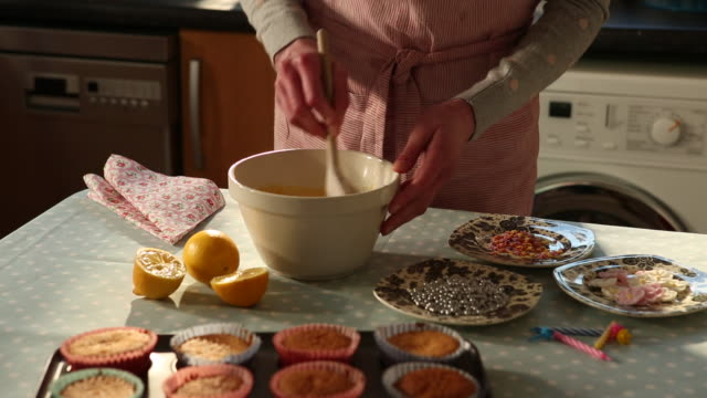 MS Shot of woman checking glazing mixture for cupcake / London, Greater London, United Kingdom