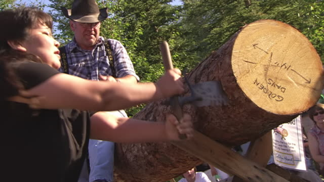MS Shot of woman competing in log sawing contest at Golden Days Festival in Pioneer Park / Fairbanks, Alaska, United States