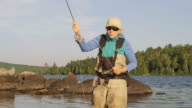 MS Shot of Woman fly fishing at long Pond / Maine, United States