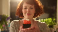 CU R/F Shot of Woman holding up cupcake and smiling / London, Greater London, United Kingdom