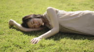 MS Shot of Woman lies at lawn in park and relaxing / Uji, Kyoto, Japan
