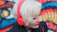 CU Shot of Woman listening to music over headphones in front of graffiti / Berlin, Germany