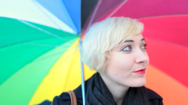 MS Shot of Woman looking towords and twirling rainbow color umbrella / Berlin, Germany