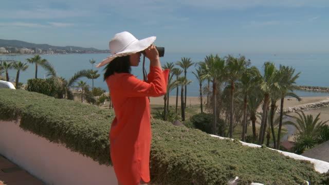 MS PAN Shot of woman looking with binoculars / Marbella, Andalusia, Spain