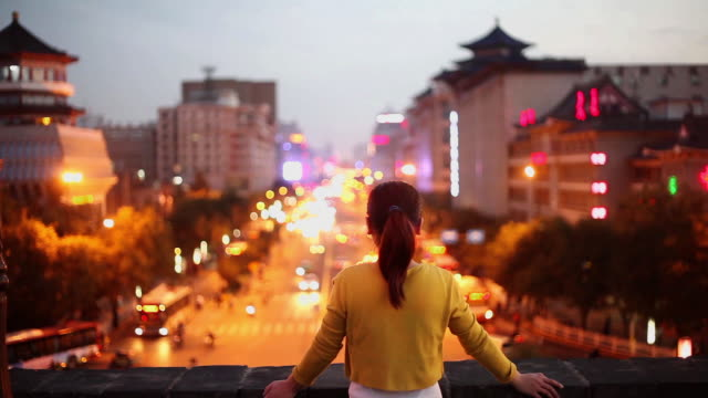 MS Shot of woman on Xian city wall with city traffic at sunset / Xian, China