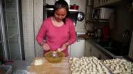 MS Shot of Woman packaging wonton in kitchen / Xian, China
