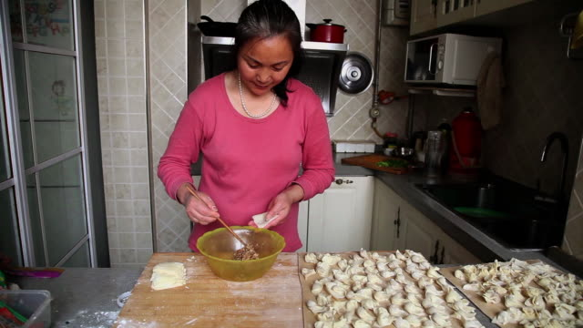 MS Shot of Woman packaging wonton in kitchen / Xian, China