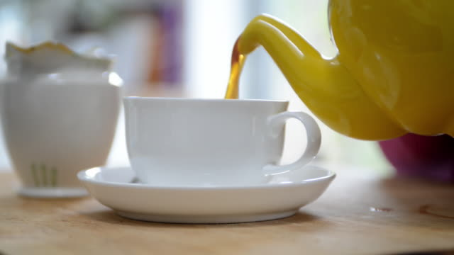 CU Shot of woman pouring tea into cup / London, Greater London, United Kingdom