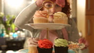 CU Shot of Woman putting cupcake on cake stand and sprinkles decoration on top of cake / London, Greater London, United Kingdom