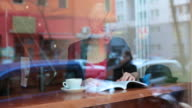 MS Shot of Woman reading book at window in cafe / Berlin, Germany