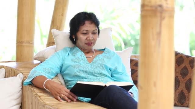 MS Shot of woman reading book / Ubud, Bali, Indonesia