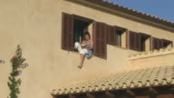 MS Shot of woman relaxing and reading book at holiday villa / Puerto Pollenca, Mallorca, Balearic Islands, Spain