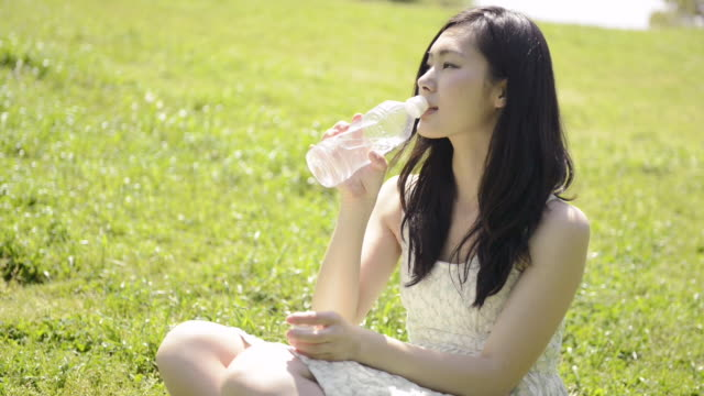 MS Shot of Woman sits down on lawn and drinks water / Uji, Kyoto, Japan
