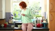 MS Shot of Woman sitting on kitchen worktop looking at ipad while making tea, having breakfast / London, United Kingdom