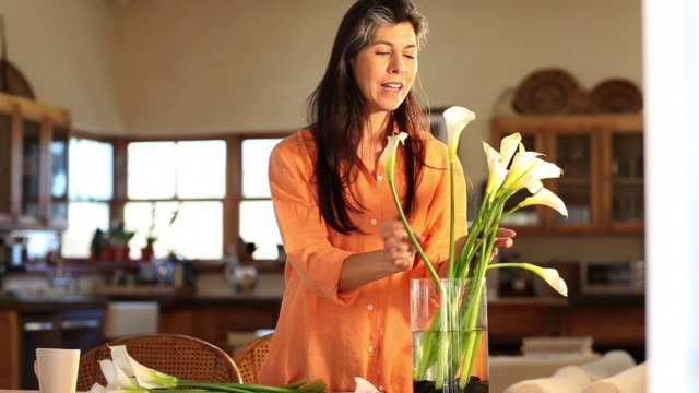 MS Shot of woman smelling and arranging flowers in vase at home / Lamy, New Mexico, United States