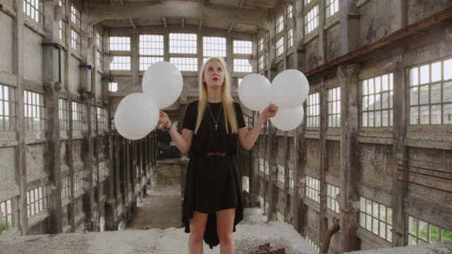 'WS SLO MO Shot of Woman standing on upper floor of abandoned factory holding balloons / Berlin, Germany'