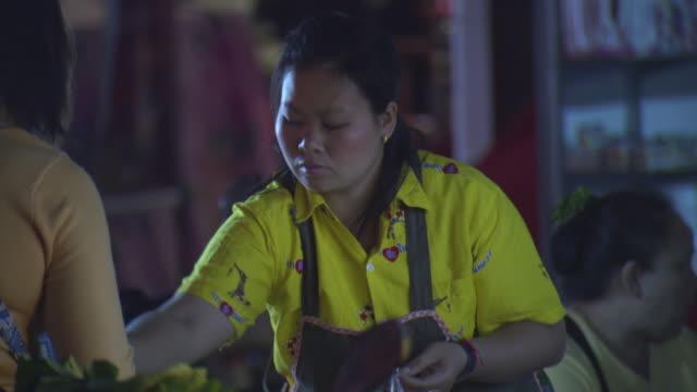 MS TU Shot of Woman street vendor places food inside plastic bag at her stall on Mae Sai main street at night / Mae Sai, Chiang Rai, Thailand