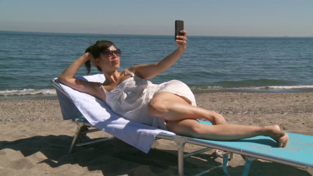 MS Shot of woman take selfie on beach / Marbella, Andalusia, Spain