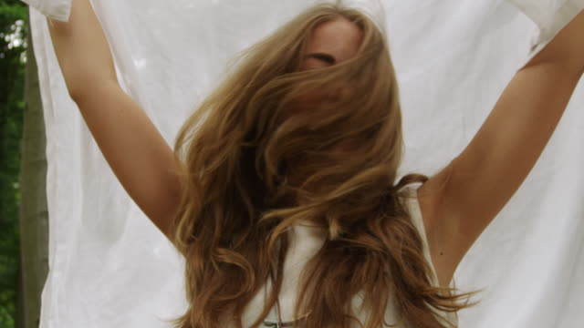 'CU SLO MO Shot of Woman unfolding white sheet over her head, laughing and shaking her hair in forest / Berlin, Germany'