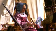 MS Shot of woman wearing bonnet spins wool into yarn using spinning wheel / Fairfax, Virginia, United States