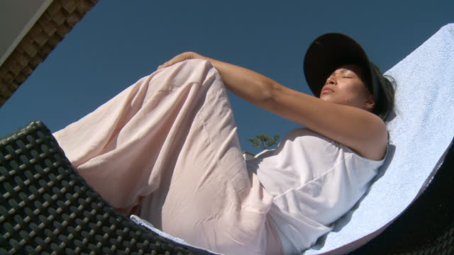 MS LA Shot of woman with cap sunbathing in rocking chair / Marbella, Andalusia, Spain