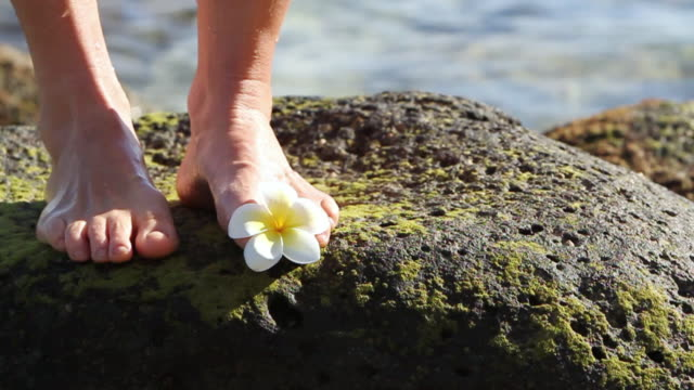 CU Shot of woman with plumeria flower between toes / Paia, Hawaii, United States