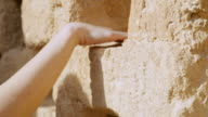 CU TU Shot of woman's hand touching dove homes at Masada in Negev desert / Israel