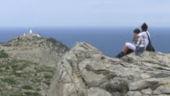 WS Shot of women and girl sitting and looking at Cap Formentor / Puerto Pollenca, Mallorca, Balearic Islands, Spain