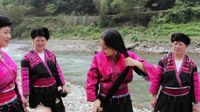MS PAN Shot of Women preparing their hair near river / Yao Village, Huangluo, China