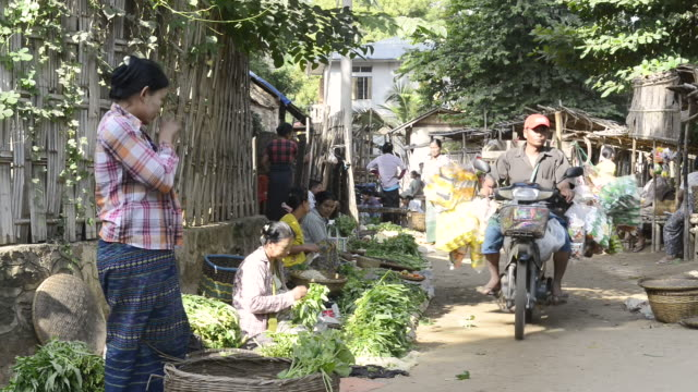 MS Shot of Women selling vegetables and a motorbike with goods is driving on myinkaba market / Bagan, Mandalay Division, Myanmar