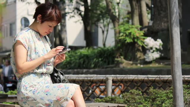 MS Shot of women using smartphone at park / Asakusa, Tokyo, Japan