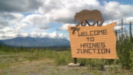 MS Shot of Wooden Welcome to Haines Junction roadside sign with wooden black bear and mountain range in back side on Haines Junction near Kluane National Park and Reserve / Haines Junction, Yukon, Canada