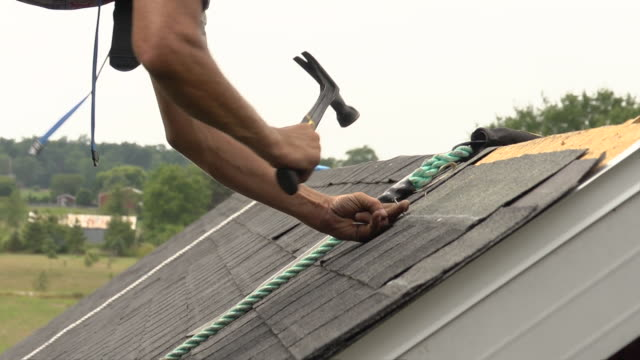 MS Shot of worker hammering on roof / Chelsea, Michigan, United States