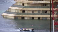 MS Shot of Workers on raft pass by grounded Costa Concordia cruise ship / Giglio Porto, Tuscany, Italy