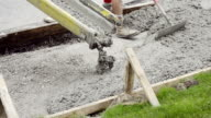 MS Shot of Workmen spreading and leveling concrete being poured for sidewalk / Valparaiso, Indiana, United States