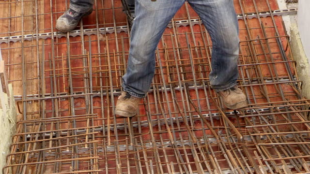 MS Shot of workmen still road tying in metal wire at house construction / Hermeskeil, Rhineland-Palatinate, Germany
