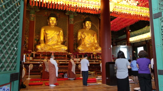 MS Shot of Worshippers inside Jogyesa Temple / Seoul, South Korea