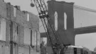 MS Shot of wrecked building with crane swinging iron ball to knock down wall in front of Manhattan Bridge