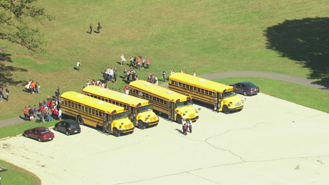 MS AERIAL Shot of yellow school buses on parking lot with students outside at Valley Forge National Park / King of Prussia, Pennsylvani,a United States