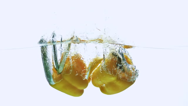 CU TD SLO MO Shot of Yellow Sweet Pepper, capsicum annuum, Vegetable falling into Water against White Background / Calvados, Normandy, France