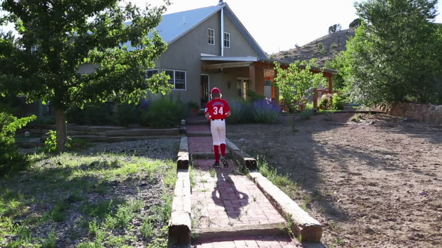 MS Shot of young baseball player walking up to his home / Santa Fe, New Mexico, United States