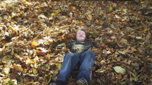 MS ZI SLO MO Shot of young boy playfully balls backward into pile of leaves / Hillsboro, Oregon, United States