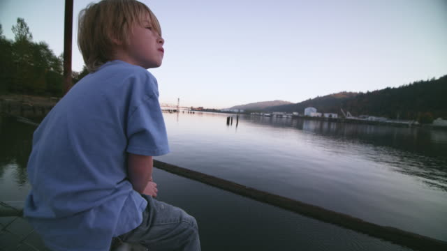 MS SLO MO Shot of young boy sitting on dock looking over river and off into distance with city is in distance / Portland, Oregon, United States