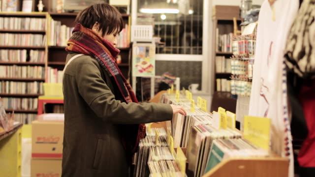 MS Shot of young female browsing and picking up vinyl record / Nakagusuku, Okinawa, Japan