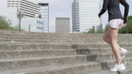 MS TU SLO MO Shot of young female jogger running up steps / Portland, Oregon, United States