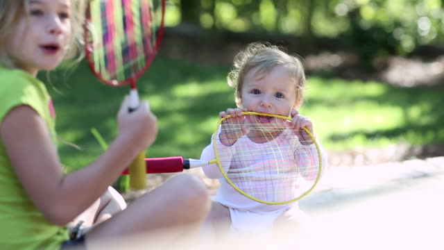 MS Shot of young girl and her baby brother holding badminton rackets / St Simon's Island, Georgia, United States