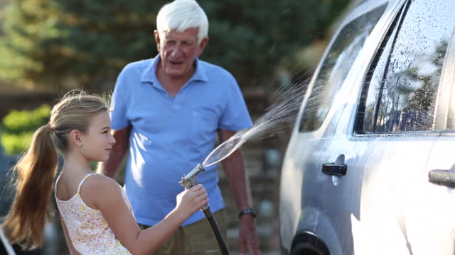 MS PAN Shot of young girl and her grandfather washing their car / Santa Fe, New Mexico, United States